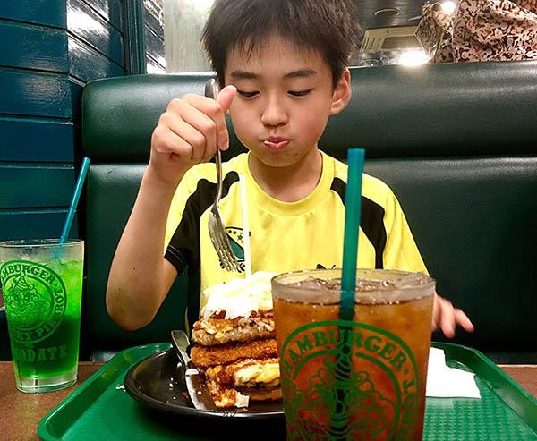 ボリューミーでおおきなハンバーガーを美味しそうに食べる少年