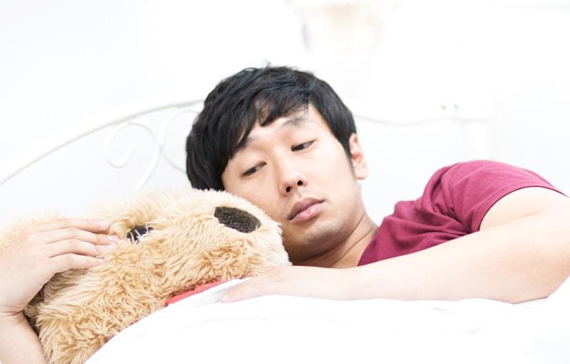 クマの縫いぐるみと寝る男