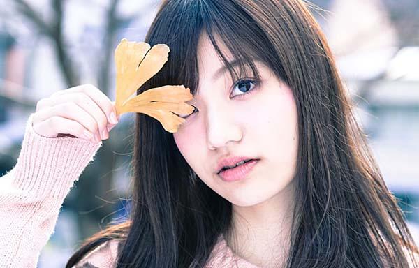 イチョウの葉で目を隠す女性