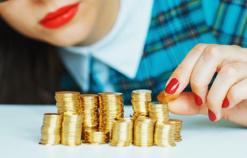 お金を積み上げる女性
