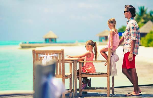 娘2人と海を眺める父親