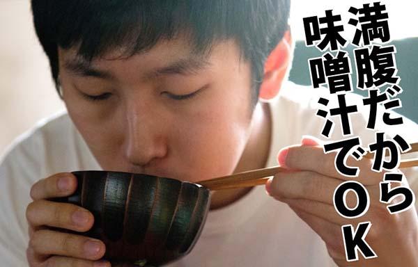 味噌汁をすする男
