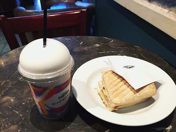 コーヒーと一緒にサンドイッチを食べる