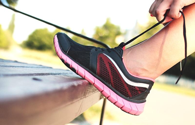 ジョギングで靴ひもを結ぶ女性