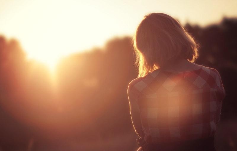 夕日を見てたそがれている女