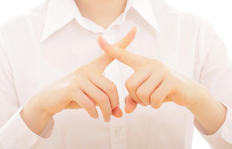 指でNGサインを出す女