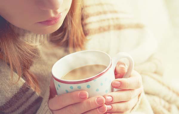 暖かいコーヒーを飲む女性