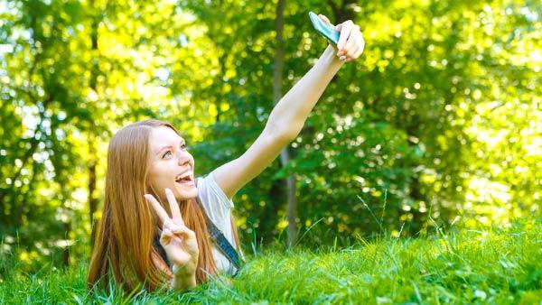 草の上で自撮りする女性