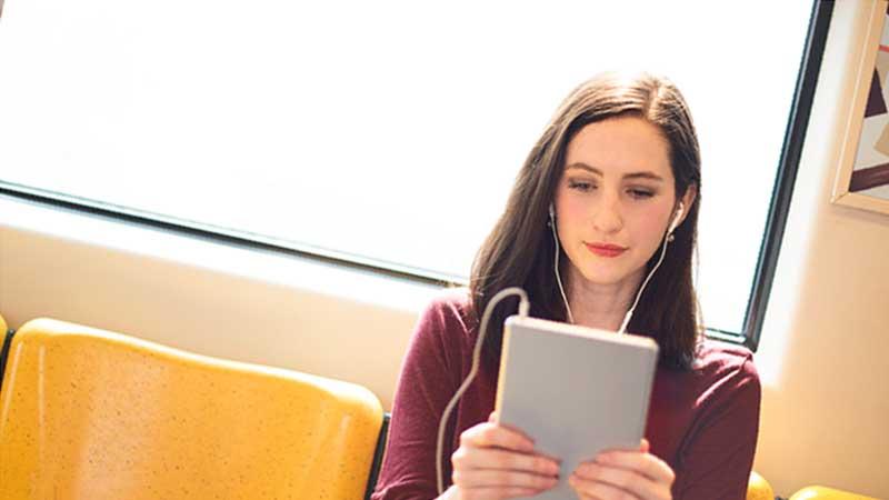 電車でタブレット作業をする女性