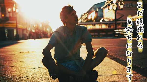 夕日の下空を見上げる男