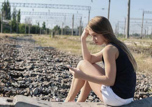 スマホ持ち悲しんでいる女性