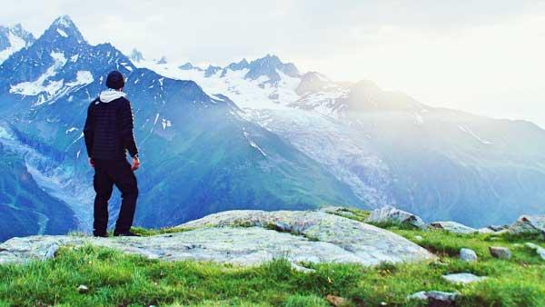 山から景色を眺める男