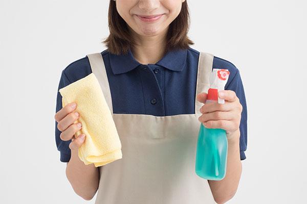 洗剤と雑巾を持つ女性