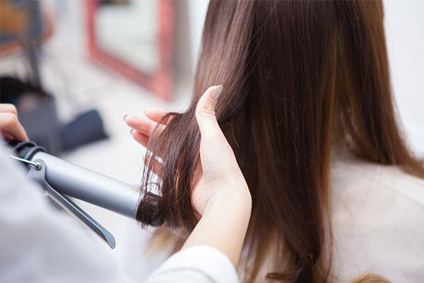 ヘアアイロンをあてる女性美容師