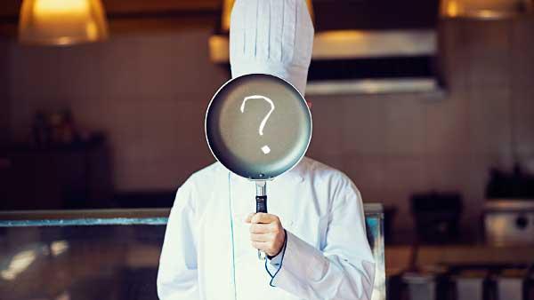 フライパンで顔を隠した料理人
