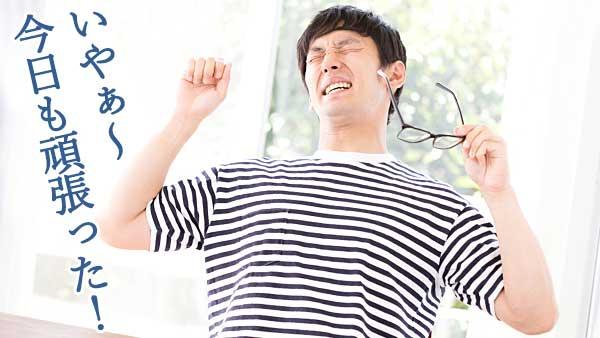 眼鏡をはずし伸びをする男