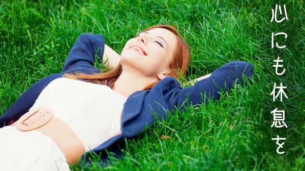 草原の上に寝そべる女性