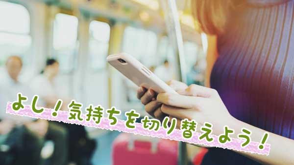 電車での通勤中にスマホを見る女性