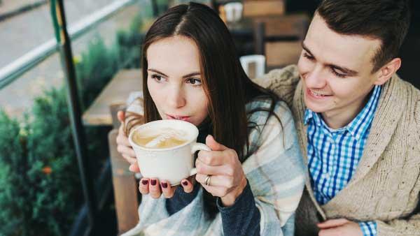 コーヒーを飲む彼女と笑顔の彼氏