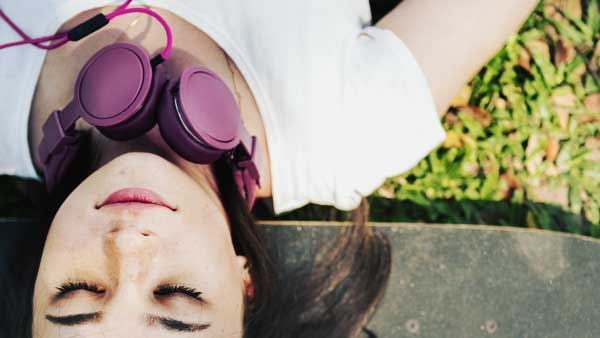 ヘッドフォンを首にかけ眠る女性