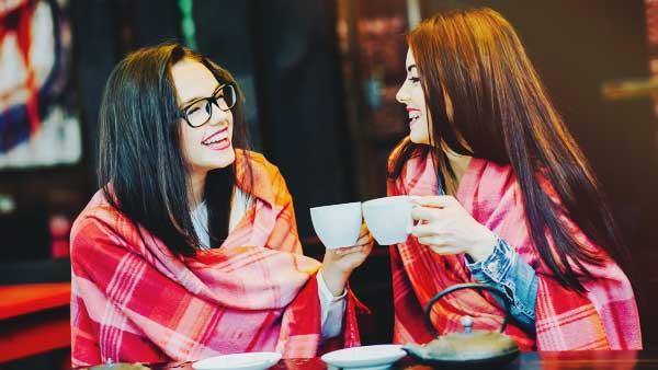 笑顔で友達とコーヒーで乾杯する女性