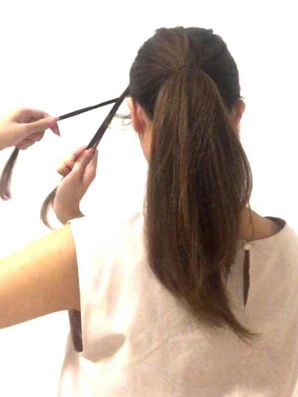 残しておいた両サイドの毛束をねじってアメピンで固定する女性の髪の毛