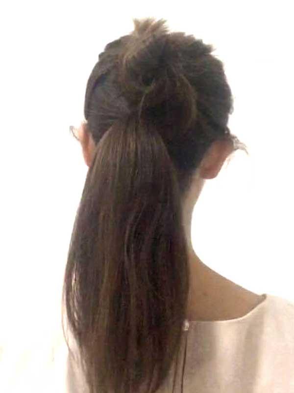 耳の位置より上の髪をゴムで仮留めして、残りの髪をポニーテールにする女性の髪の毛