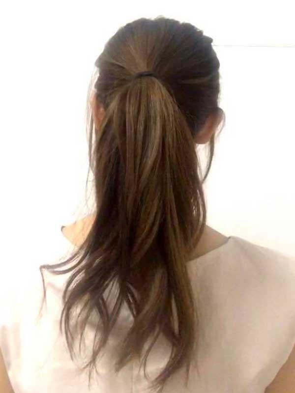髪をこめかみの位置の高さでポニーテールにする女性