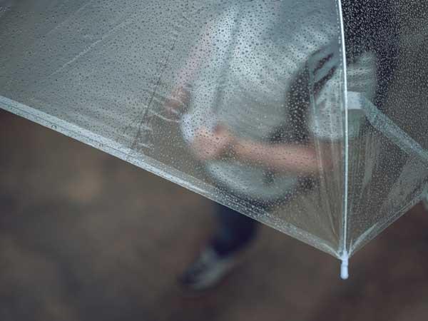 傘をさしながら歩く女性