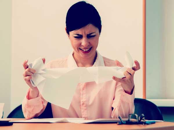 紙を破りイライラしている女性