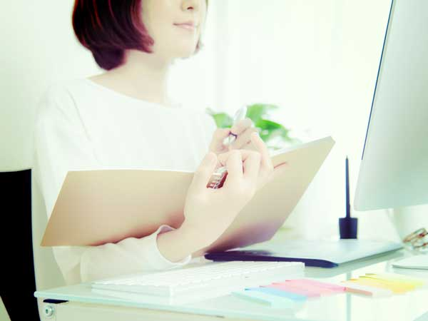課題をノートに書き出す女性