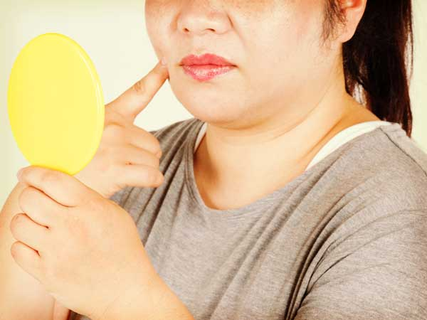 鏡を見る太っている女性