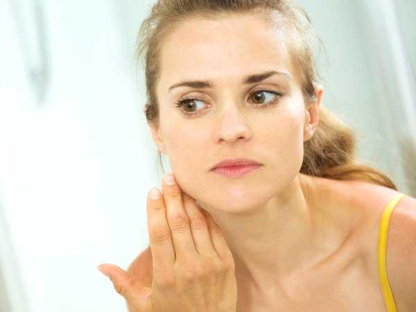 鏡を見るスキンケアする女性