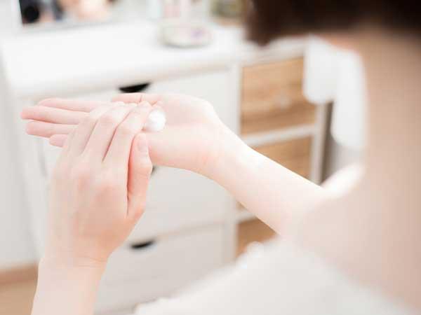 保湿クリームを手のひらにのせる女性