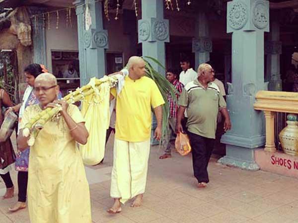 黄色い布で包まれ運ばれる赤ちゃん