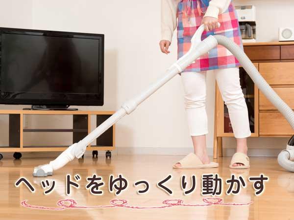 掃除機のヘッド部分をゆっくり動かして掃除する女性