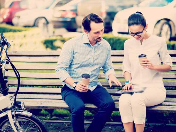 ベンチに座ってタブレットをいじる男女
