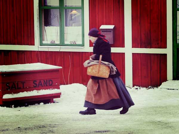 外を歩く中世の衣装を着た女性スタッフ