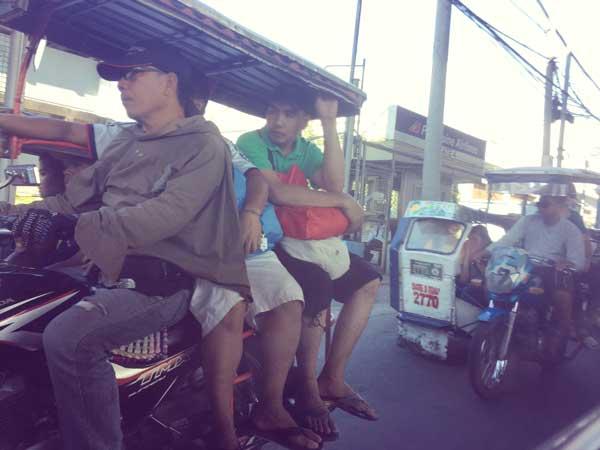乗り合いバスのジプニーで移動する人