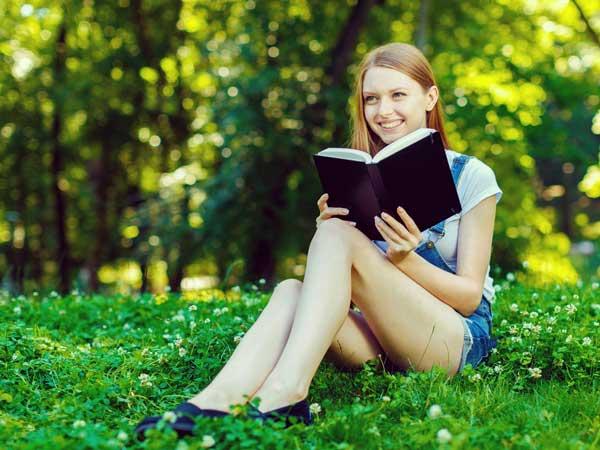 芝の上で読書する女性