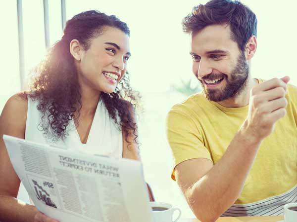 新聞を読みながら会話をしているカップル
