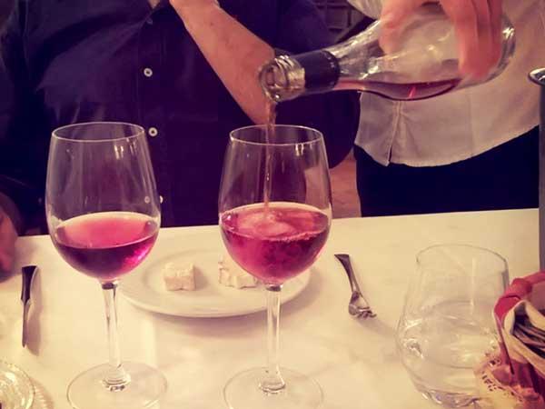 現地のフレンチレストランでグラスに注がれる赤ワイン