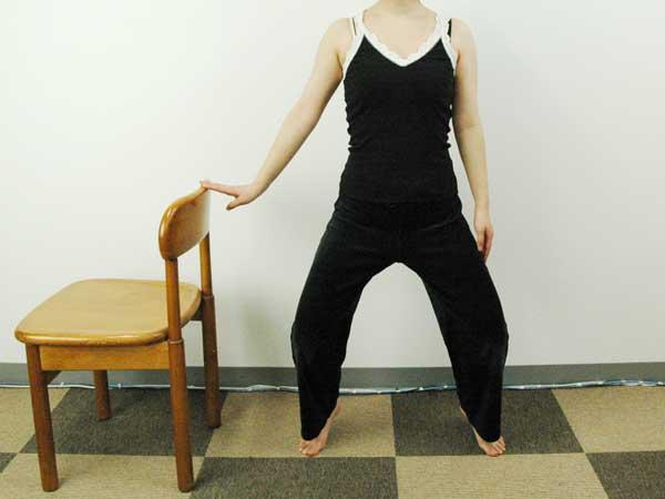 正面から見た椅子に掴まり立った状態で爪先立ちエクササイズを実践している様子