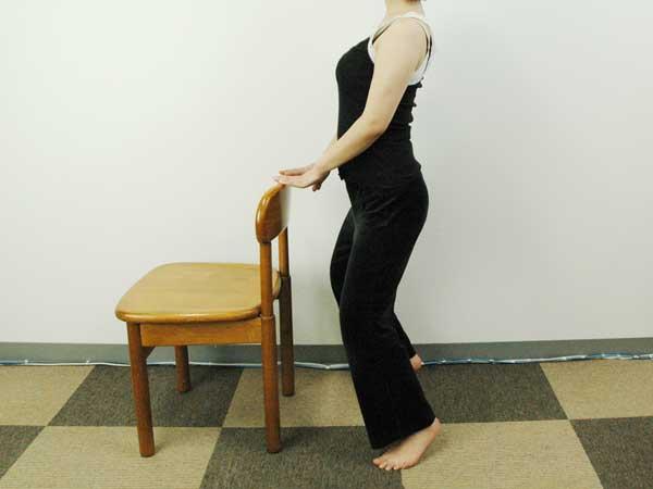 横から見た椅子に掴まり立った状態で爪先立ちエクササイズを実践している様子