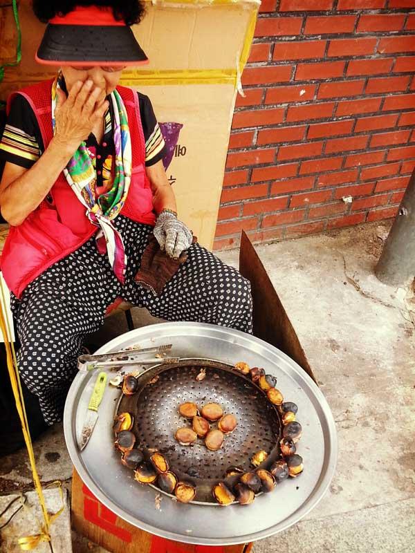 釜山の海雲台の街中で焼き栗を売っている年配の女性