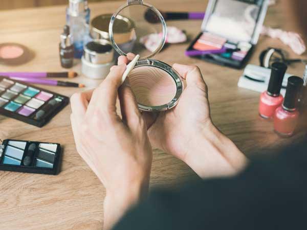 化粧品を手に持つ女性