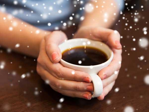 暖かい飲み物を持つ女性の手