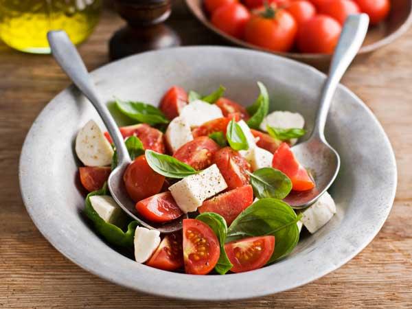 イタリア料理の前菜のトマトとモッツアレーラチーズとバジルの盛り合わせ