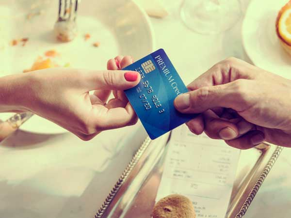 テーブルでクレジットカードで支払いをしている女性