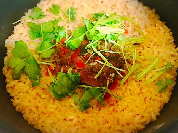 炊きあがった秋刀魚とカリカリ梅の本格炊き込みごはんに三つ葉をのせた状態